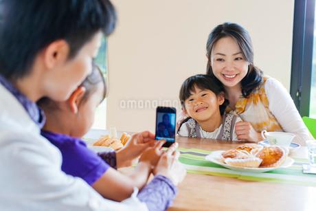 テーブルを挟んで写真を撮る2組の母と子の写真素材 [FYI02832198]