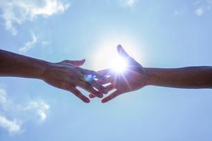 青空と太陽と伸ばした2人の手の写真素材 [FYI02832220]