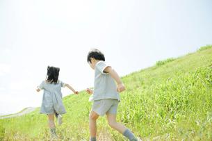 草原を走る2人の幼稚園児の写真素材 [FYI02832300]