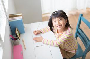 机で勉強する小学生の女の子の写真素材 [FYI02832364]