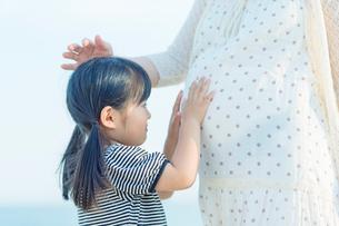 妊婦の母のお腹を触る娘の写真素材 [FYI02832502]