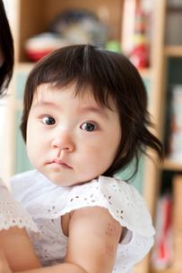 お母さんに抱っこされて泣きやんでまっすぐ見つめる赤ちゃんの写真素材 [FYI02833053]