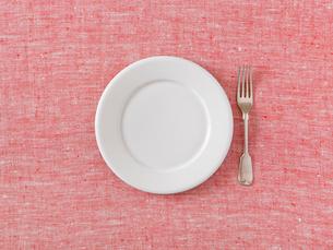 赤と白の布と白い皿とフォークの写真素材 [FYI02833445]