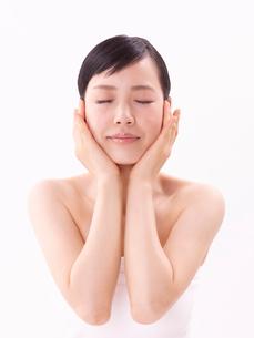 頬に手をそえスキンケアをする女性の写真素材 [FYI02833536]