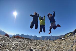 山頂でジャンプする山ガールの写真素材 [FYI02833610]