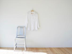 壁にかかった白いシャツと椅子の写真素材 [FYI02833732]