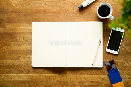 テーブルに置かれたノートとコーヒーとスマートフォンの写真素材 [FYI02833739]