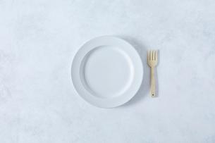 白とグレーで塗装された背景と白い皿とカトラリーの写真素材 [FYI02833746]