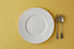 黄色の麻の布と白い皿とフォークとスプーンの写真素材 [FYI02833816]