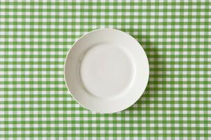 きみどりのチェックのテーブルクロスと白い皿の写真素材 [FYI02833874]