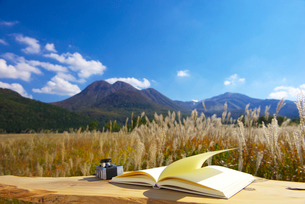 白紙の本とカメラと九重連山の写真素材 [FYI02833918]