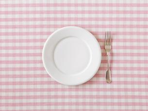 ピンクと白のチェックの布と白の丸い皿とフォークの写真素材 [FYI02833930]
