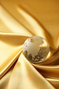 シルクの布に置かれた地球儀の写真素材 [FYI02834273]