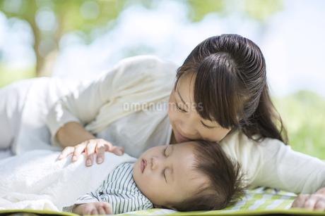 眠る赤ちゃんに寄り添う母親の写真素材 [FYI02834370]