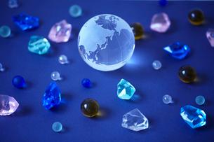 青バックに透明な地球儀とカラフルな石の写真素材 [FYI02835010]