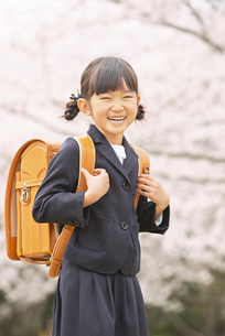 ランドセルを背負った笑顔の小学生の女の子と桜の写真素材 [FYI02835609]