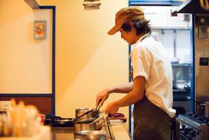 鉄板カウンターで調理する若いシェフの写真素材 [FYI02835724]