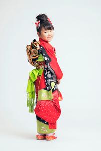 振り向いて笑顔を見せる着物の女の子の写真素材 [FYI02835803]