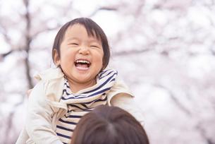 母親に抱っこされる笑顔の子供と桜の写真素材 [FYI02835891]