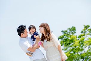 公園で娘を抱く両親の写真素材 [FYI02837902]