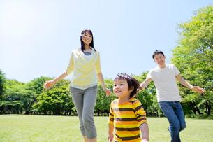 公園を走る3人家族の写真素材 [FYI02837950]