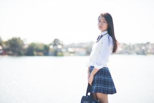 水辺に立っている制服姿の女子高生の写真素材 [FYI02838011]