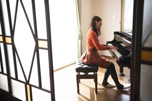 部屋でピアノを弾いている女性の写真素材 [FYI02838036]