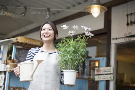お花の鉢を持って笑っている女性の写真素材 [FYI02838046]
