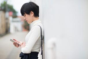 街でスマホを見ている女性の写真素材 [FYI02838061]