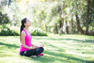 緑の中で瞑想をしている女性の写真素材 [FYI02838074]