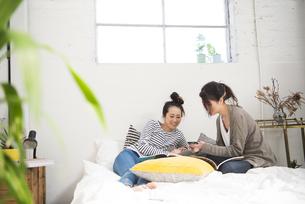 ベッドの上で話している女性2人の写真素材 [FYI02838077]