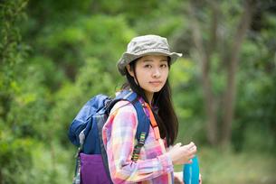 森の中で振り返っている女性の写真素材 [FYI02838079]