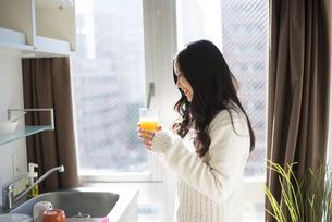 キッチンでオレンジジュースを持っている女性の写真素材 [FYI02838084]