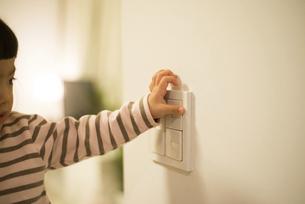 照明のスイッチを押そうとしている女の子の写真素材 [FYI02838086]