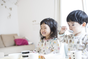 朝ごはんを食べている双子の写真素材 [FYI02838105]