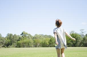 芝生の上を歩いている女性の写真素材 [FYI02838115]
