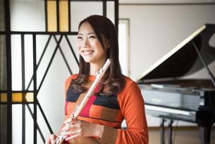 ピアノの前でフルートを持っている女性の写真素材 [FYI02838138]