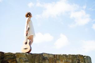 岩の上をギターを持って歩いている女性の写真素材 [FYI02838151]