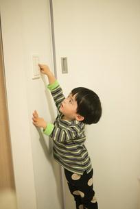 照明のスイッチを消そうとしている男の子の写真素材 [FYI02838156]