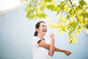ストレッチをしているトレーニングウェアの女性の写真素材 [FYI02838186]