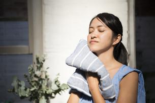 顔をタオルで拭いている女性の写真素材 [FYI02838189]