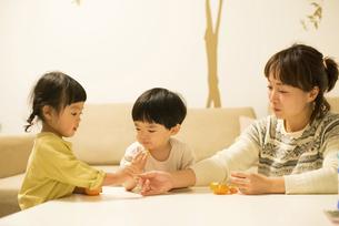 みかんを分けて食べている双子と母親の写真素材 [FYI02838196]