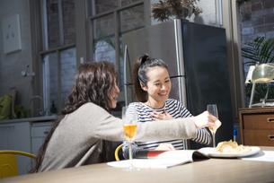 家で飲みながらおしゃべりをしている女性2人の写真素材 [FYI02838204]