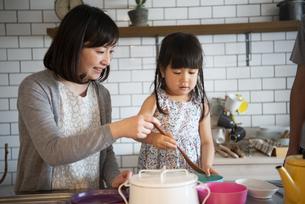 キッチンでお手伝いをしている女の子と母親の写真素材 [FYI02838238]