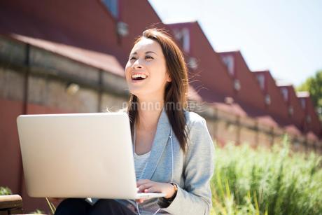 ベンチに座ってパソコンで仕事をしながら笑っている女性の写真素材 [FYI02838250]