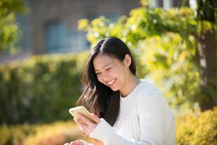 笑顔でスマホをいじっている女性の写真素材 [FYI02838263]