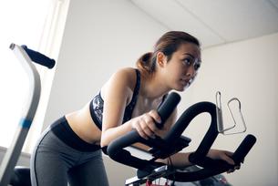 ジムでフィットネスバイクに乗っている女性の写真素材 [FYI02838264]