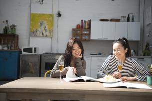 家で飲みながらおしゃべりをしている女性2人の写真素材 [FYI02838277]