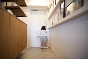 母親の靴を履いて玄関にいる女の子の写真素材 [FYI02838281]