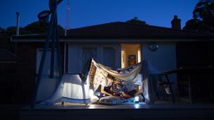シーツで作ったテントの中で本を読んでいる兄弟の写真素材 [FYI02838282]